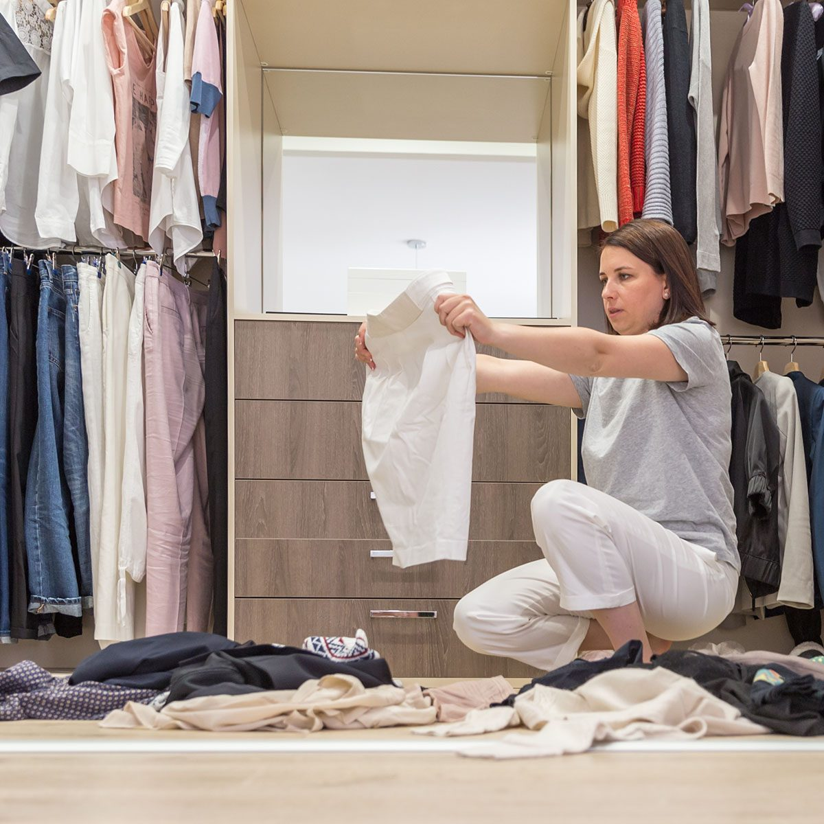 Young woman throwing clothes in walk in closet. Mess in wardrobe and dressing room concept