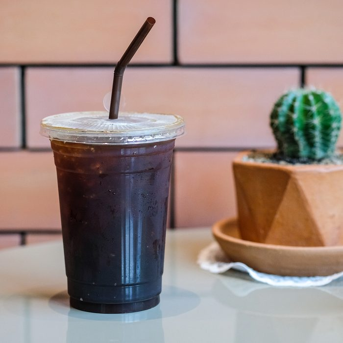 Long black coffee with ice on wooden table in coffee shop