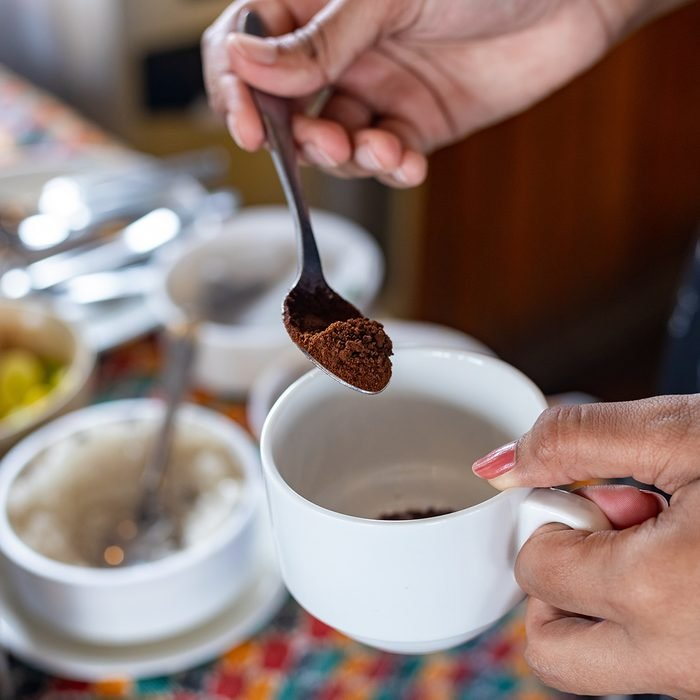Making a coffee. Adding coffee powder. Selective focus, focus on coffee powder and spoon