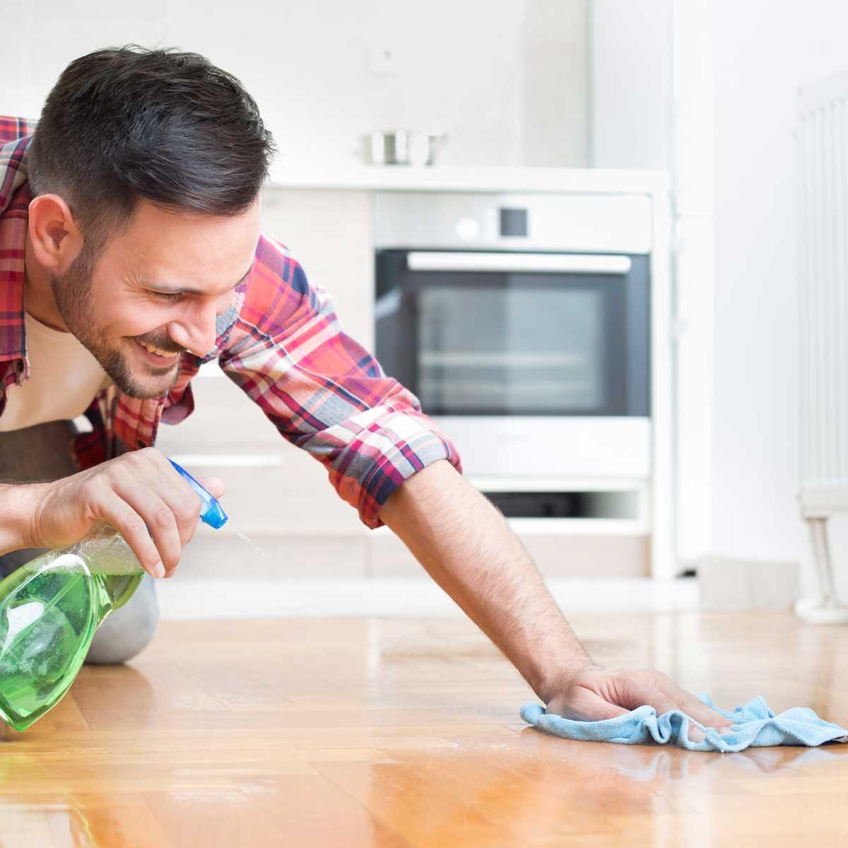 man cleaning hardwood floor