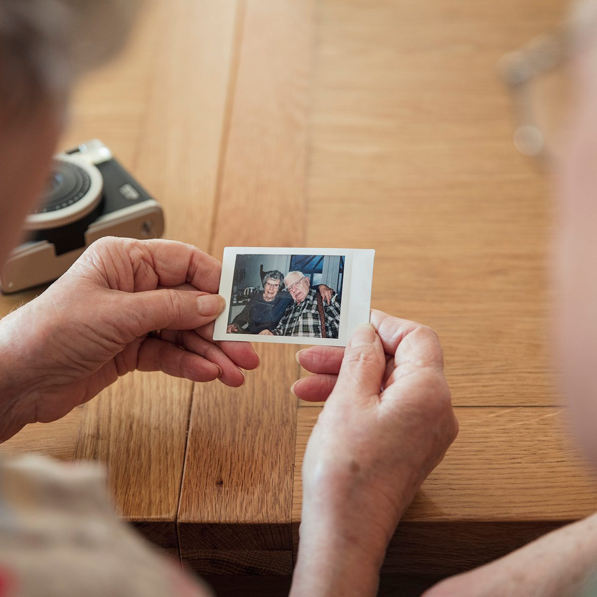 Senior couple looking at a instant film photo of themselves.