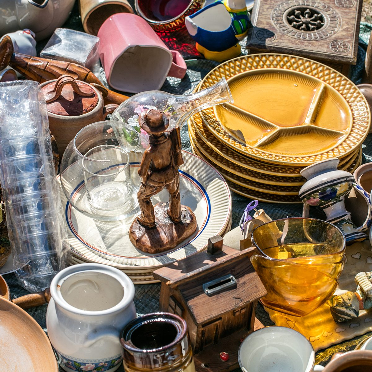 pile of household things, various dishes and decorative objects at boot sale for second hand, recycling or over-consumption society at outdoor welfare