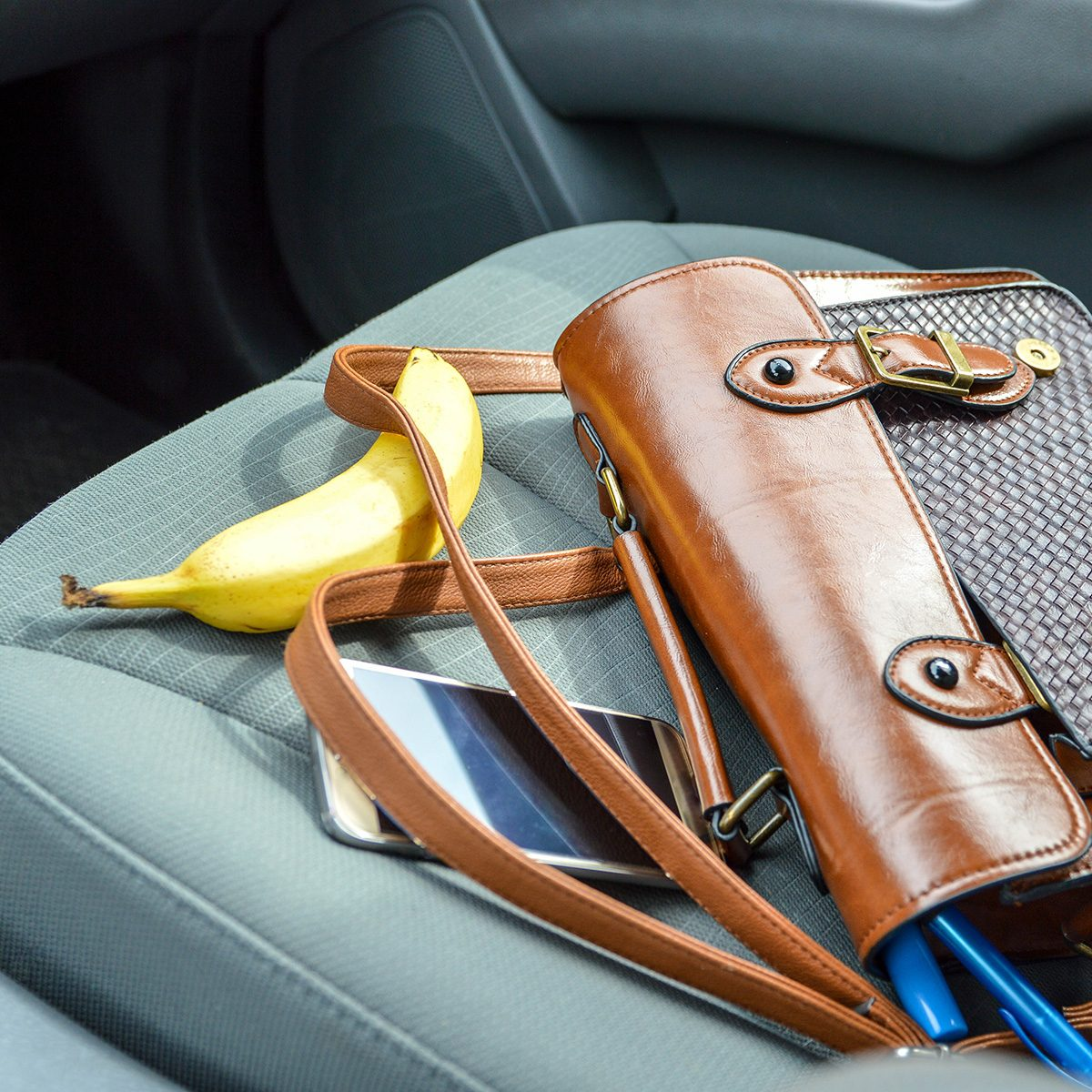 This is an image of a brown purse on the passenger seat of a car with contents spilling out. There is a pen, makeup item, phone and banana laid out around the purse. The car interior is grey.