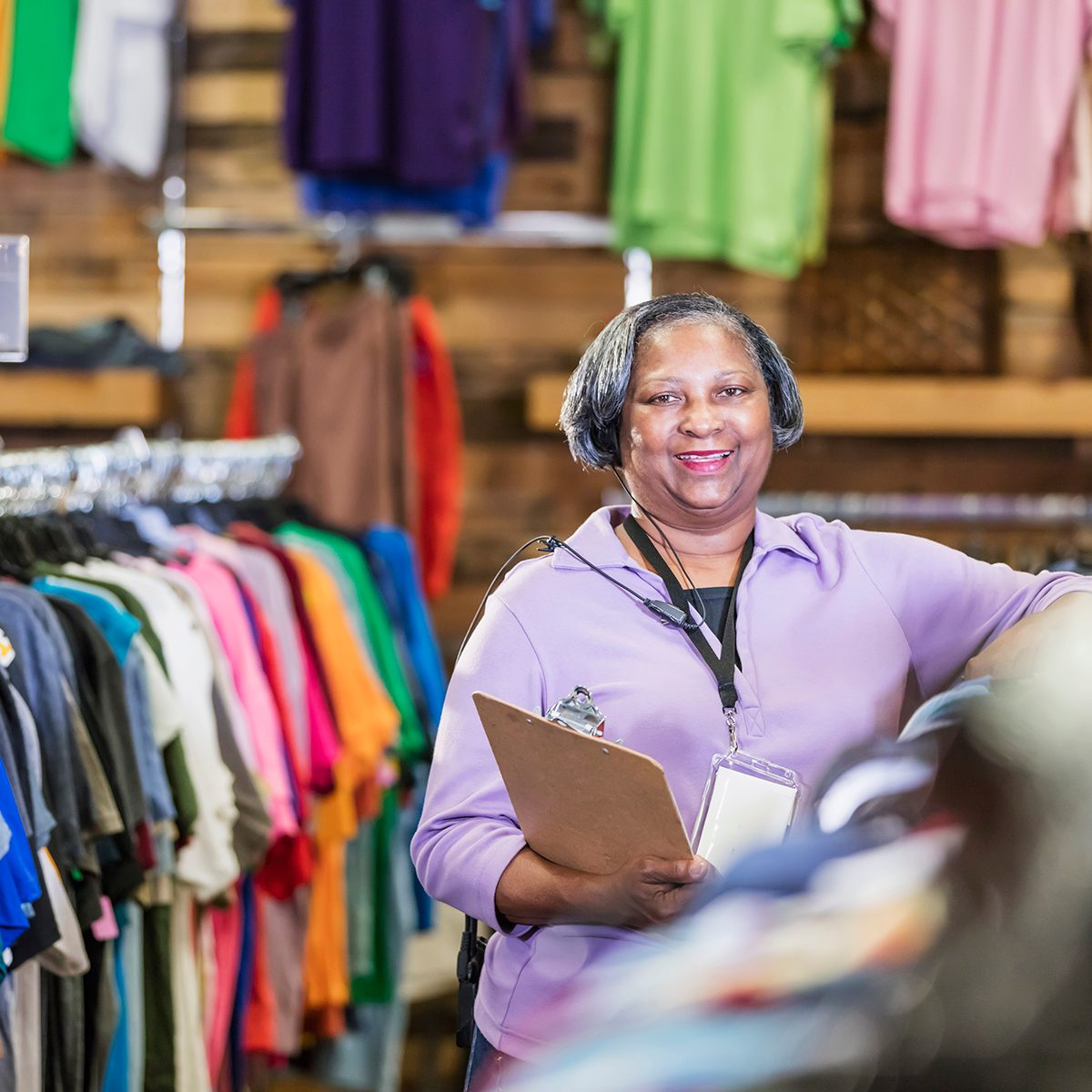 A senior African-American woman in her 60s working in a clothing store. She is standing in the menswear department at a rack of clothing, holding a clipboard.