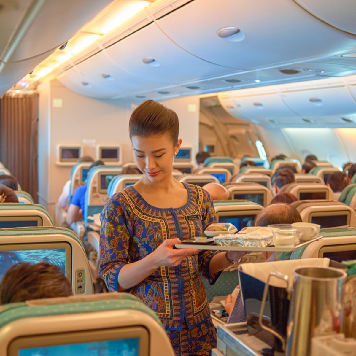 SINGAPORE - NOVEMBER 03, 2015: flight attendant serve food and drinks to passengers on board of Singapore Airlines Airbus A380; Shutterstock ID 689691664; Job (TFH, TOH, RD, BNB, CWM, CM): RD