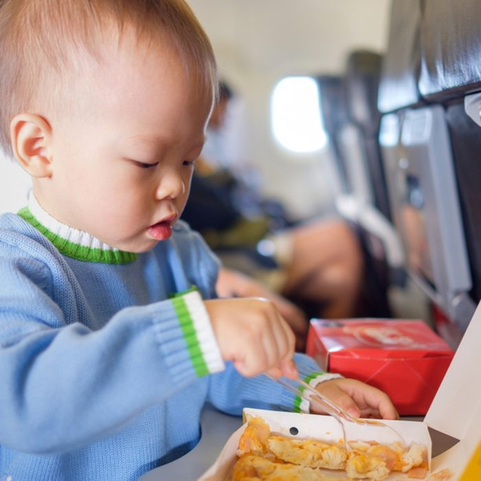 Cute little Asian 18 months / 1 year old toddler baby boy child wearing blue sweater eating food during flight on airplane. Flying with children, Happy air travel with kids & little traveler concept; Shutterstock ID 794633467; job: Job (TFH, TOH, RD, BNB, CWM, CM)