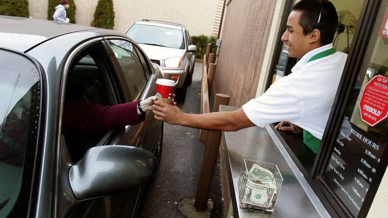 WHEELING, IL - DECEMBER 28: Starbucks worker Freddie Arteaga assists a customer with her drink order at a Starbucks drive-thru December 28, 2005 in Wheeling, Illinois. Starbucks opened 354 drive-thru stores in the U.S. in the past year, which brought for the first time, the number of new drive-thrus to comprise more than half of all new Starbucks company operated stores opened nationwide. (Photo by Tim Boyle/Getty Images)