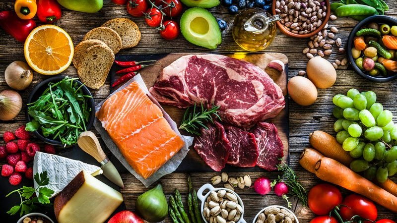 Food backgrounds: top view of a rustic wooden table filled with different types of food. At the center of the frame is a cutting board with beef steak and a salmon fillet and all around it is a large variety of food like fruits, vegetables, cheese, bread, eggs, legumes, olive oil and nuts. DSRL studio photo taken with Canon EOS 5D Mk II and Canon EF 70-200mm f/2.8L IS II USM Telephoto Zoom Lens