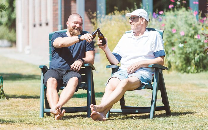 Two Smiling Men (young And Old) Drinking Beer In The Summer Garden   Best Friends (father And Son) Toasting And Laughing Together   Family And Father's Day Celebration Concept