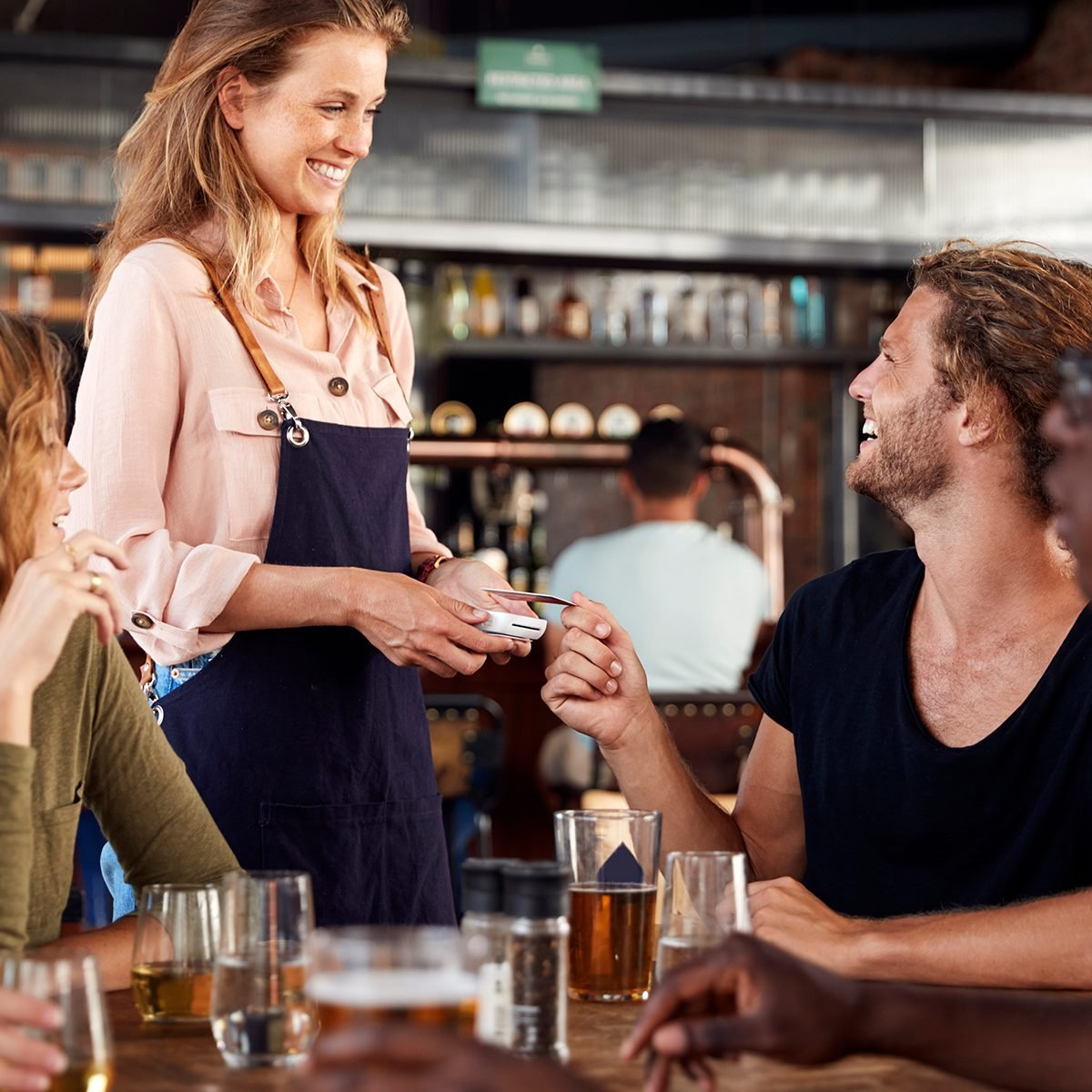 Waitress Holds Credit Card Machine As Customer Pays Bill In Bar Restaurant
