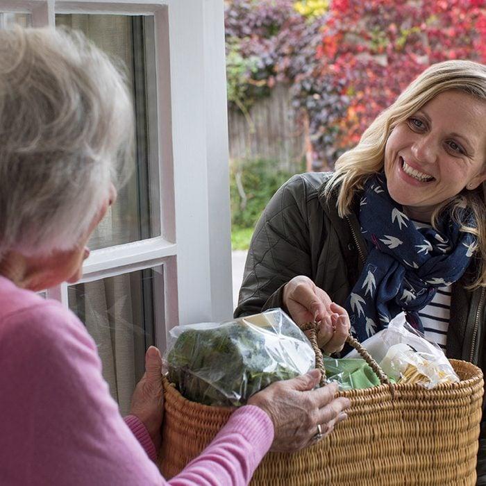 Female Neighbor Helping Senior Woman With Shopping