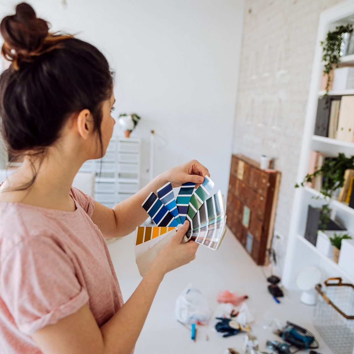 Young woman during reconstruction of apartment, holding color chart and choosing the right color for the wall