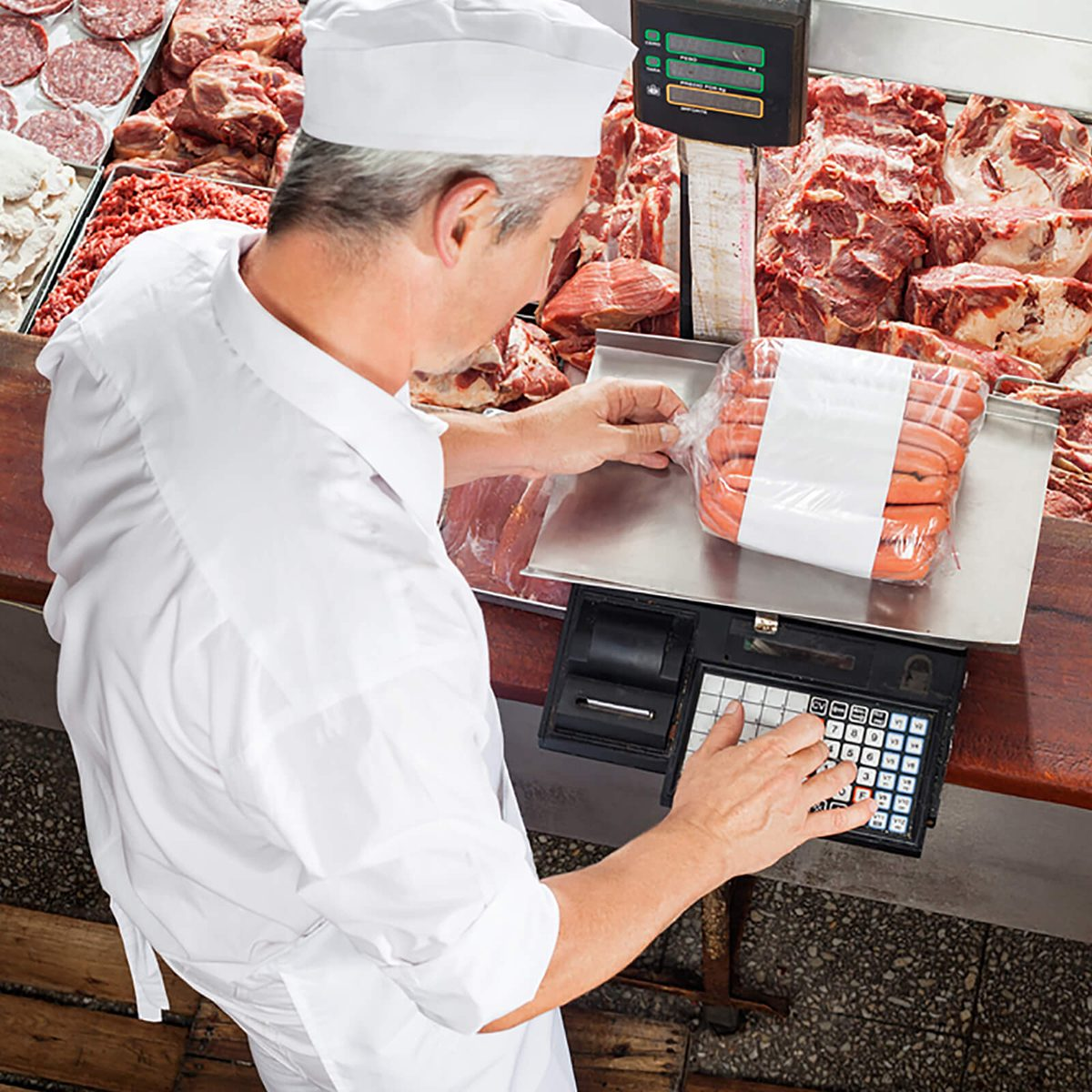 High angle view of male butcher weighing sausages at display cabinet in butchery; Shutterstock ID 242663593