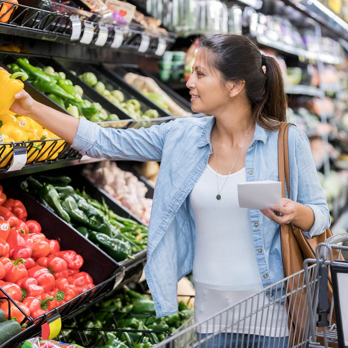 A smiling mid adult woman holds a grocery list as she shops for produce. She reaches to pick up a yellow pepper.