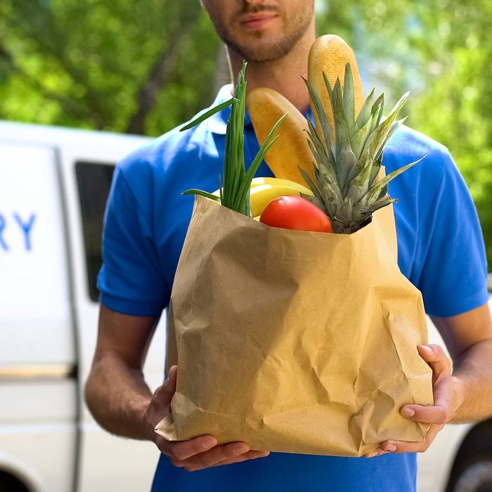 Food delivery service, male worker holding grocery bag, express food order