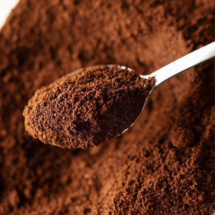 Ground coffee in spoon, natural coffee background, macro