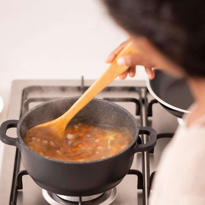High angle, over the shoulder view of a woman stirring the boiling bouillon, using a wooden spoon. The woman cooking vegetable soup in a stock pot on a gas stove. A healthy meal, lifestyle and culinary concepts.