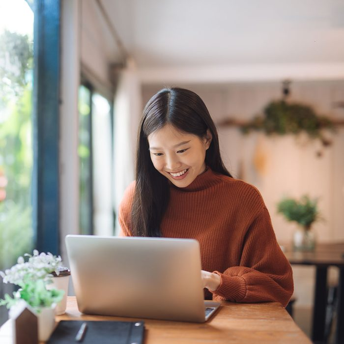 Happy young Asian girl working at a coffee shop with a laptop.