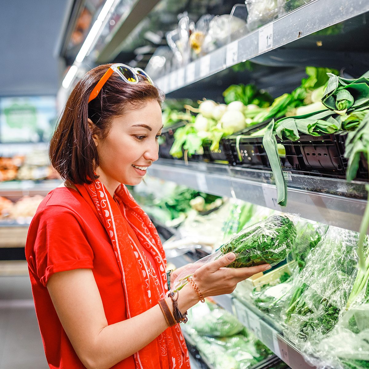 A woman in a supermarket chooses green vegetables, a concept of agriculture and a vegetarian diet