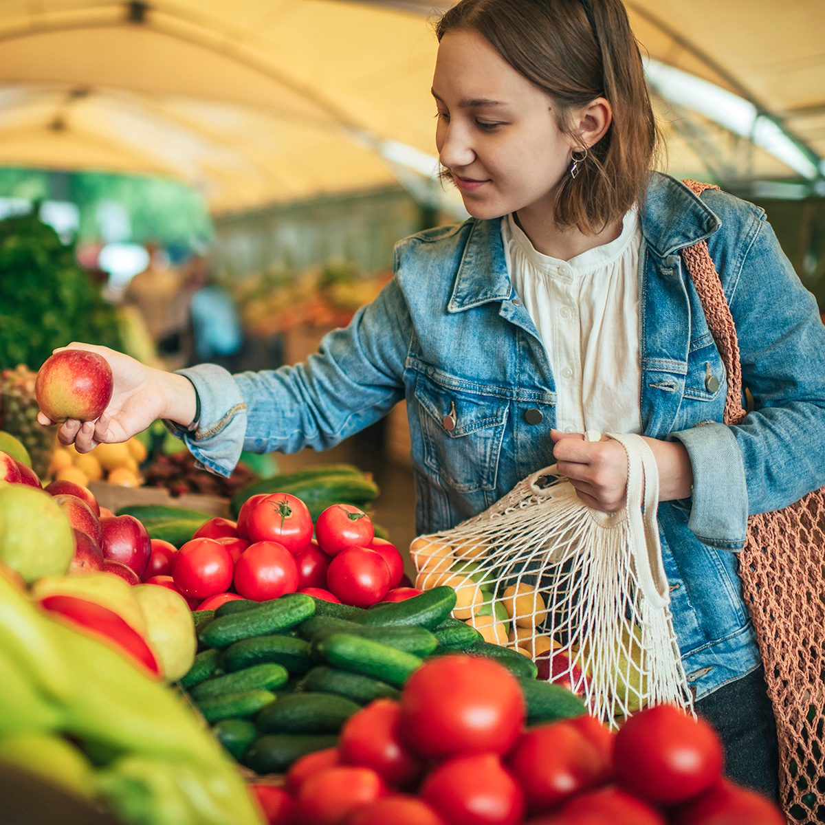 Teenager holding ecologically friendly reusable bag with fruit and vegetables