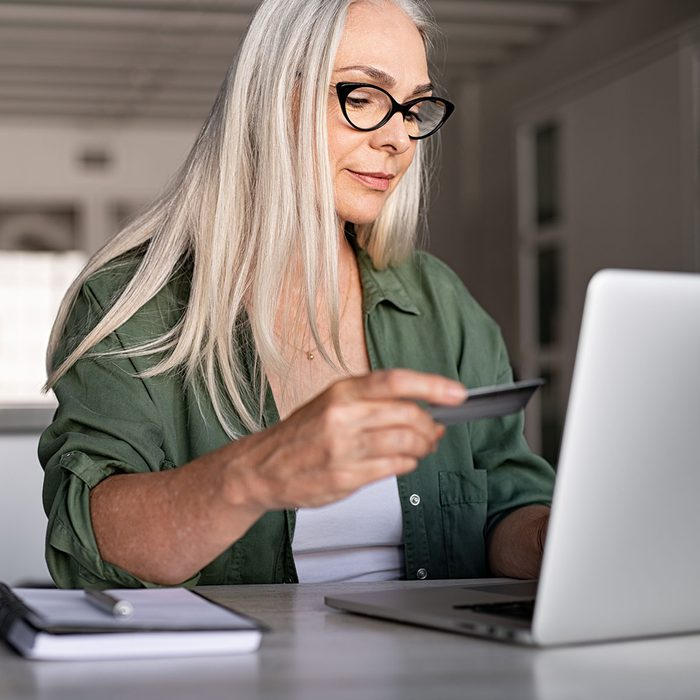 Mature woman using credit card making online payment at home. Successful old woman doing online shopping using laptop. Closeup of retired fashionable lady holding debit card for internet banking account.
