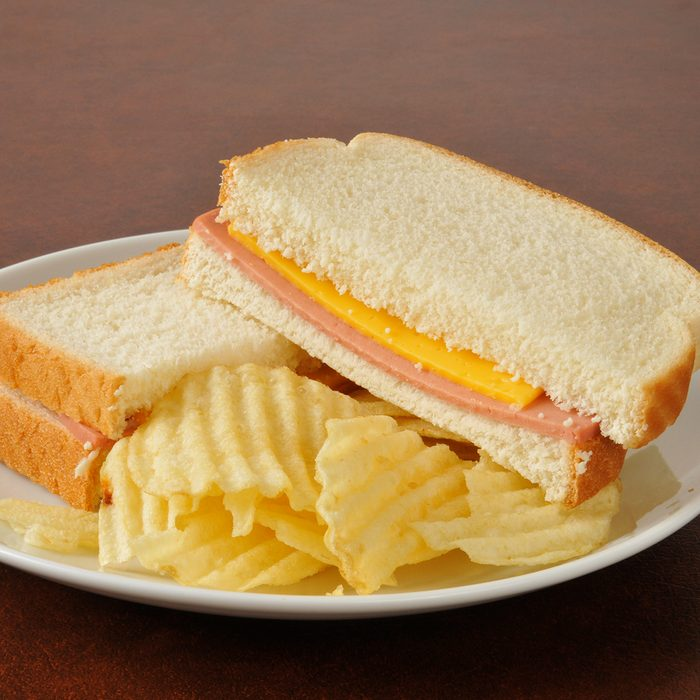 A bologna and cheese sandwich with potato chips