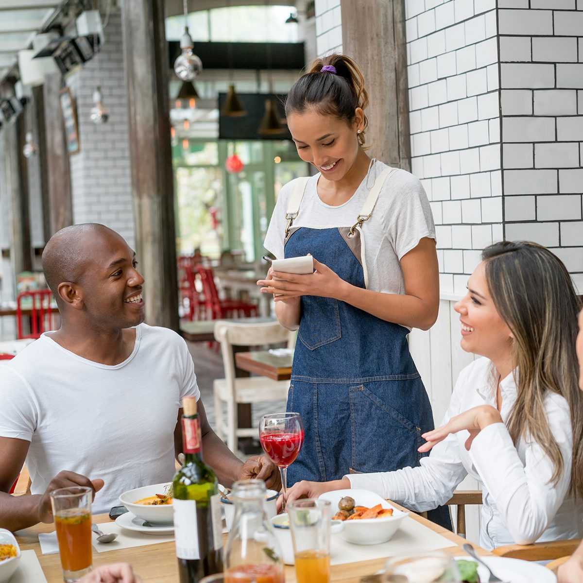 Happy waitress serving a group of people eating together at a restaurant