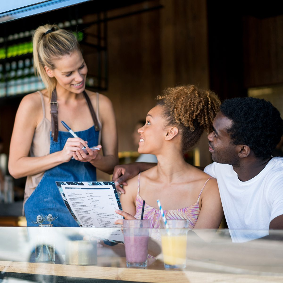 Waitress working at a restaurant and serving to a young African American couple
