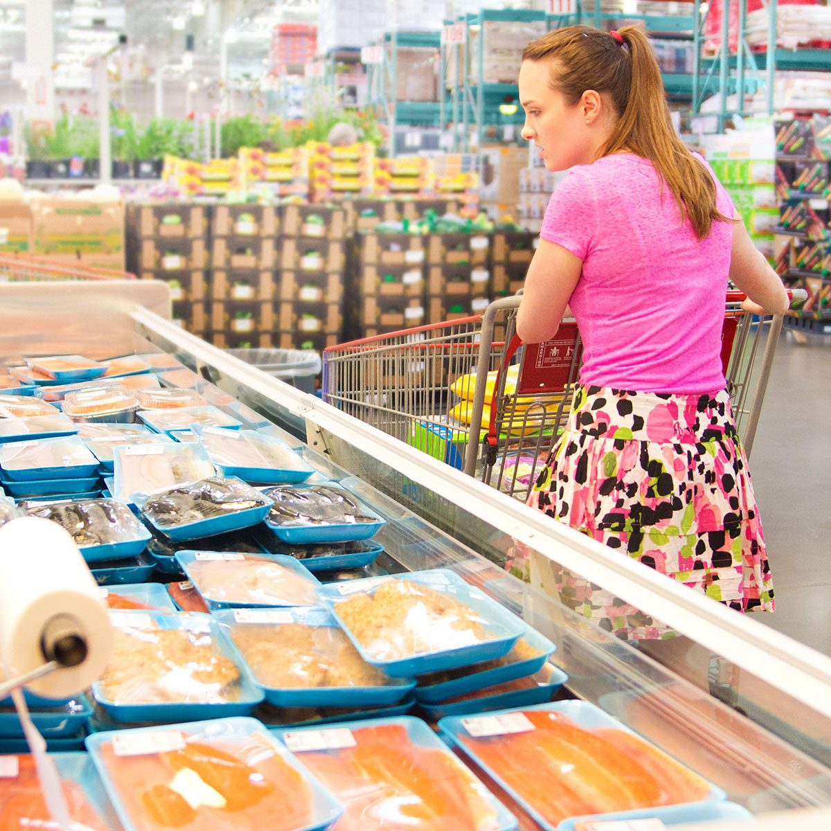 Young woman grocery shopping for fresh fish inside supermarket big box retail store. The customer looks at packaged salmon seafood in the refrigerated section refrigerator case, examining and choosing food for a healthy eating lifestyle. The consumer's shopping cart contains merchandise. Commercial products in the background are displayed for purchase.