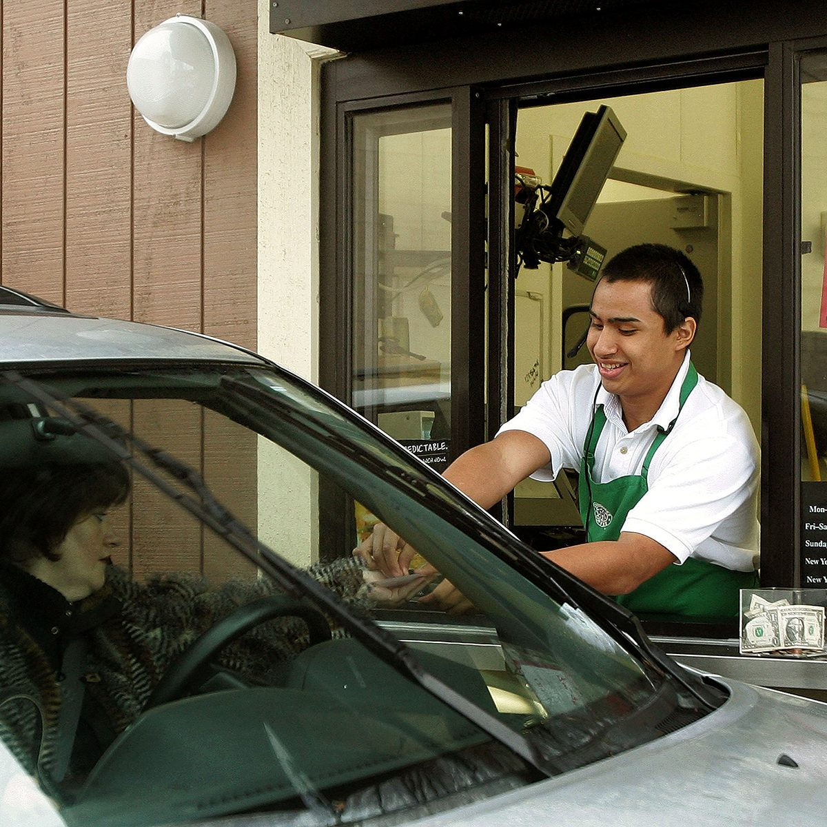 WHEELING, IL - DECEMBER 28: Starbucks worker Freddie Arteaga assists a customer with her drink order at a Starbucks drive-thru December 28, 2005 in Wheeling, Illinois. Starbucks is investing in the drive-thru market for coffee drinkers on the go. (Photo by Tim Boyle/Getty Images)