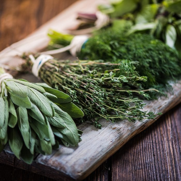 Basil, sage, dill, and thyme herbs on wooden board preparing for winter drying