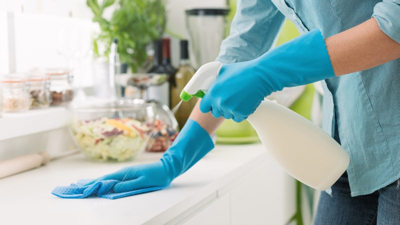 Woman cleaning and polishing the kitchen worktop with a spray detergent, housekeeping and hygiene concept