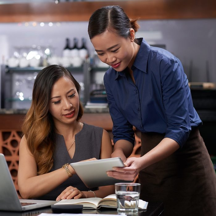 Waitress showing menu on tablet computer to visitor