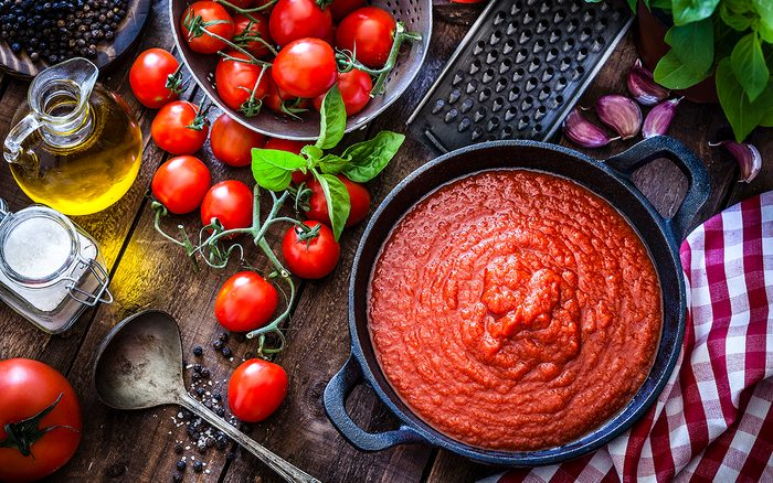 Preparing tomato sauce at home. Top view of a rustic wooden table filled with fresh ingredients for preparing tomato sauce at home. Ingredients for preparing tomato sauce are fresh ripe tomatoes, basil, olive oil, garlic, salt and pepper. The ingredients are scattered on the table all around a cast iron pan filled with prepared tomato sauce. Predominant color is red. DSRL studio photo taken with Canon EOS 5D Mk II and Canon EF 100mm f/2.8L Macro IS USM
