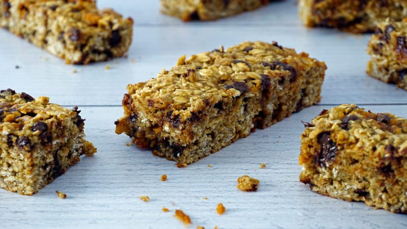 baked gluten-free granola bars scattered on weathered white wood