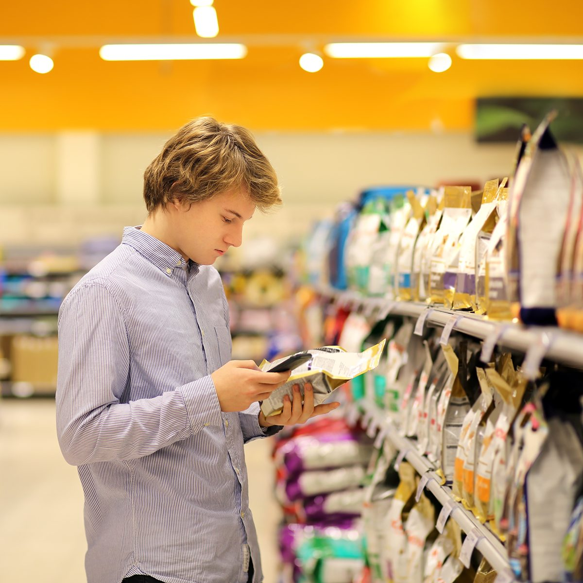 Man shopping in supermarket reading product information.Using smarthone.Pet food