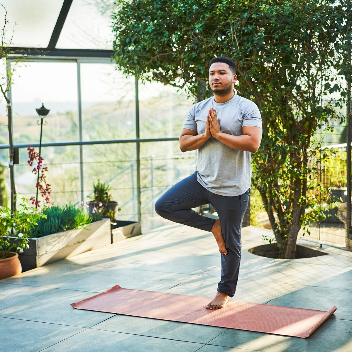 Full length of young man practicing tree pose. Male is exercising on porch. He is in sports clothing.