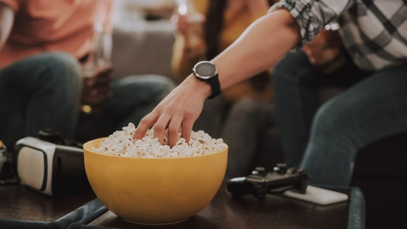 Close up of female hand with watch reaching for tasty popcorn in yellow bowl