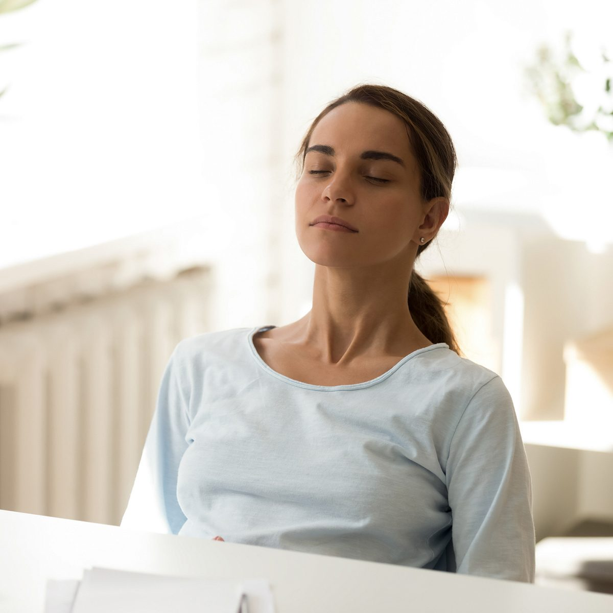 Calm stress free woman sitting at desk with eyes closed. Beautiful female relaxing on chair at work. Attractive girl lean back having rest at break time, dreaming. Harmony, stress control image concept