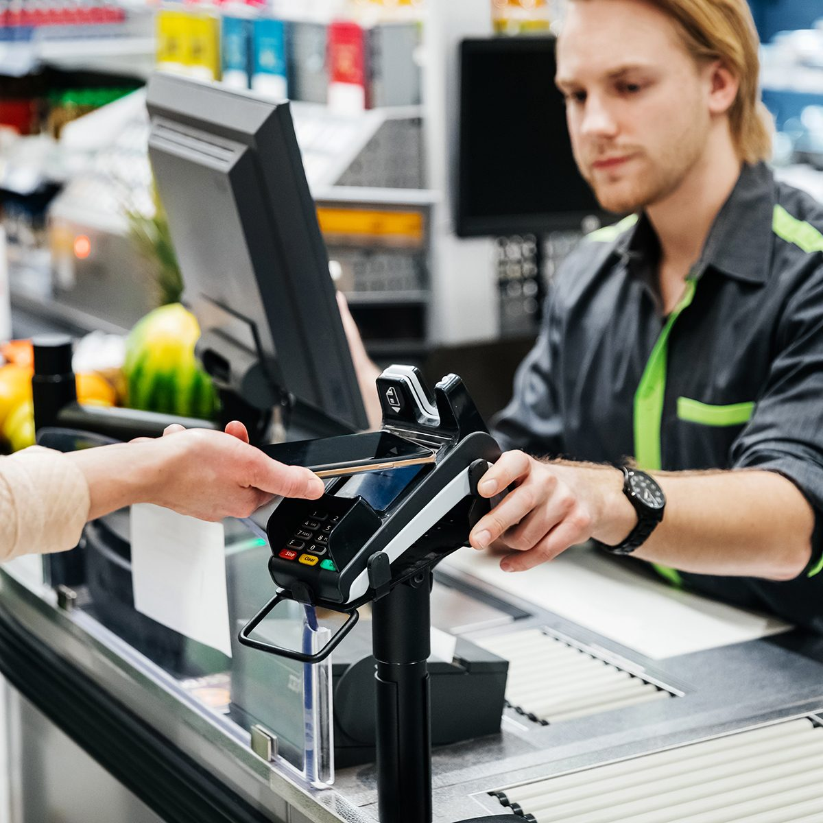 A woman paying for her groceries with her smartphone, using the contactless payment option.