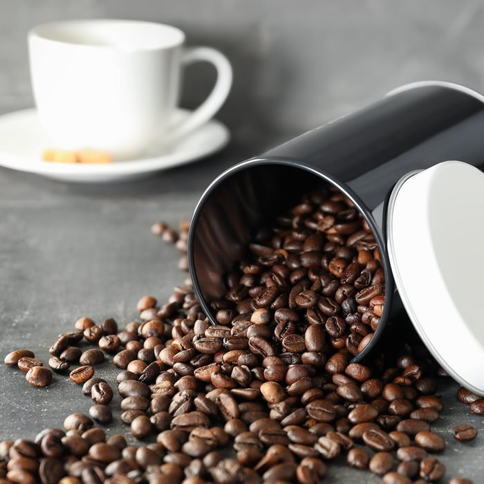 Overturned container with roasted coffee beans on table