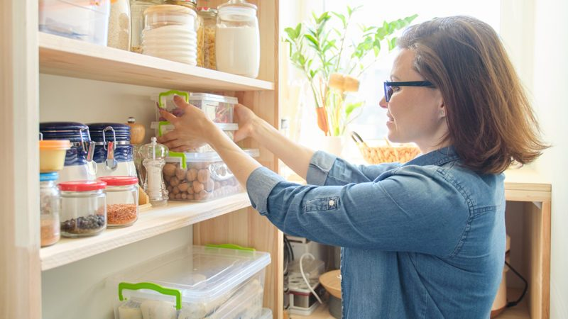 Interior of wooden pantry with products for cooking. Adult woman taking kitchenware and food from the shelves.