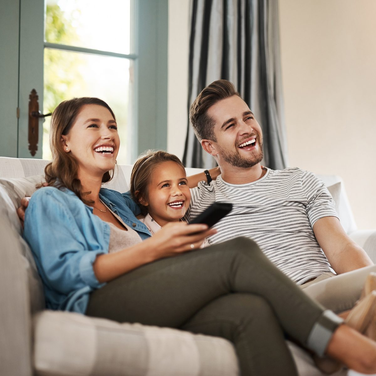 Shot of a happy young family relaxing on the sofa and watching tv together at home