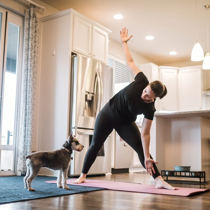 A mature adult woman does yoga and strength training exercises on a mat in her living room, her pet terrier dog keeping her company and trying to play.