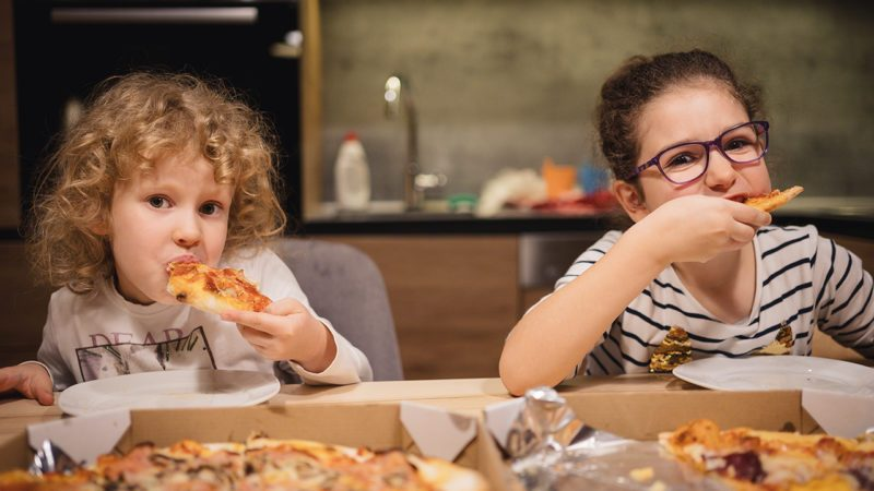 Portrait of cute little girls sitting and eating pizza