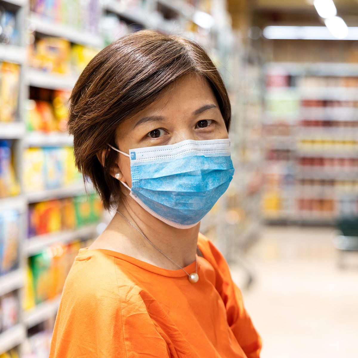 Asian women with face mask for protection against influenza virus shopping in supermarket