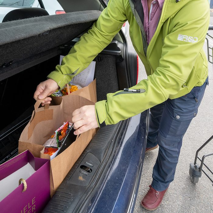 """26 March 2020, Bavaria, Deggendorf: An assistant puts a bag of food in a trunk. The woman provides food for the elderly and sick. (to dpa-Korr """"""""Happy that something like this exists"""" - shopping help for the elderly and sick"""") Photo: Armin Weigel/dpa (Photo by Armin Weigel/picture alliance via Getty Images)"""
