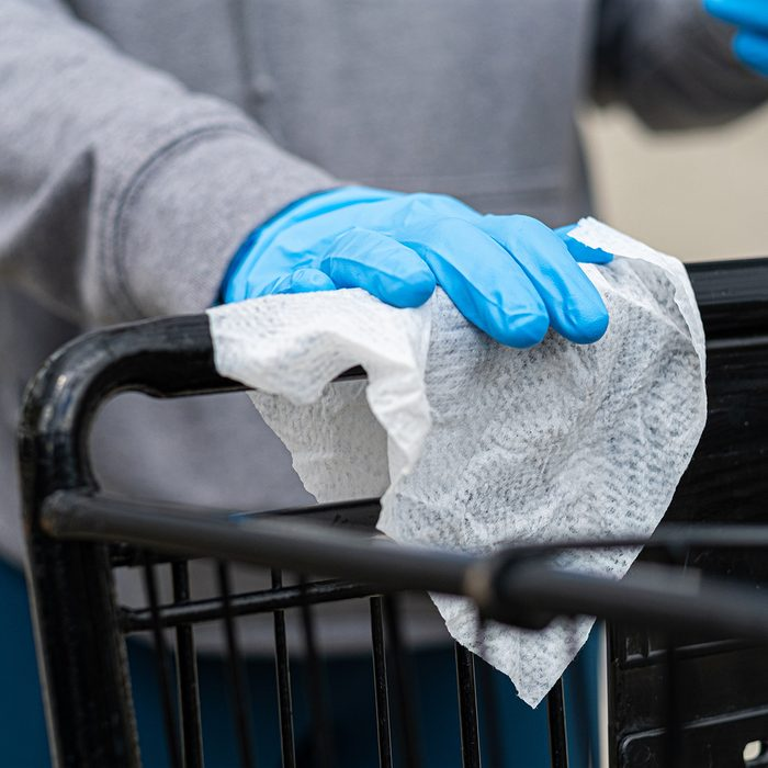 Shopper wearing gloves to prevent the coronavirus covid-19 uses a disinfecting wipe to clean the handle of a shopping cart.