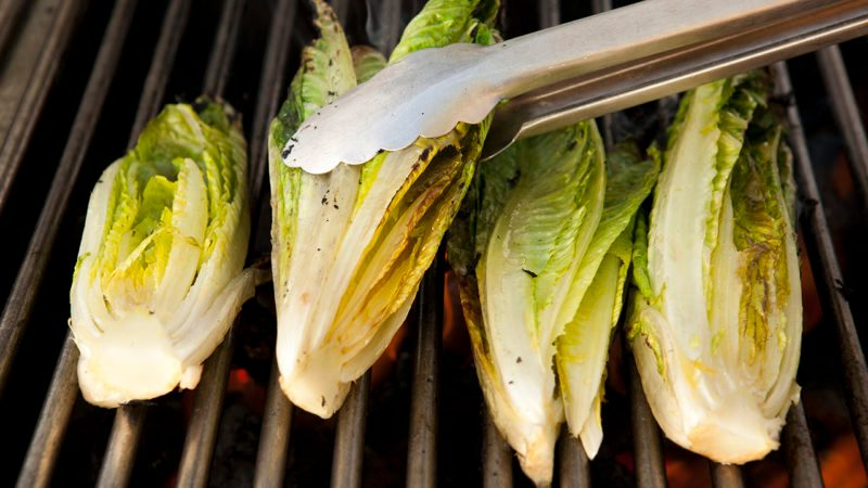 Tongs turning heads of romaine lettuce on grill