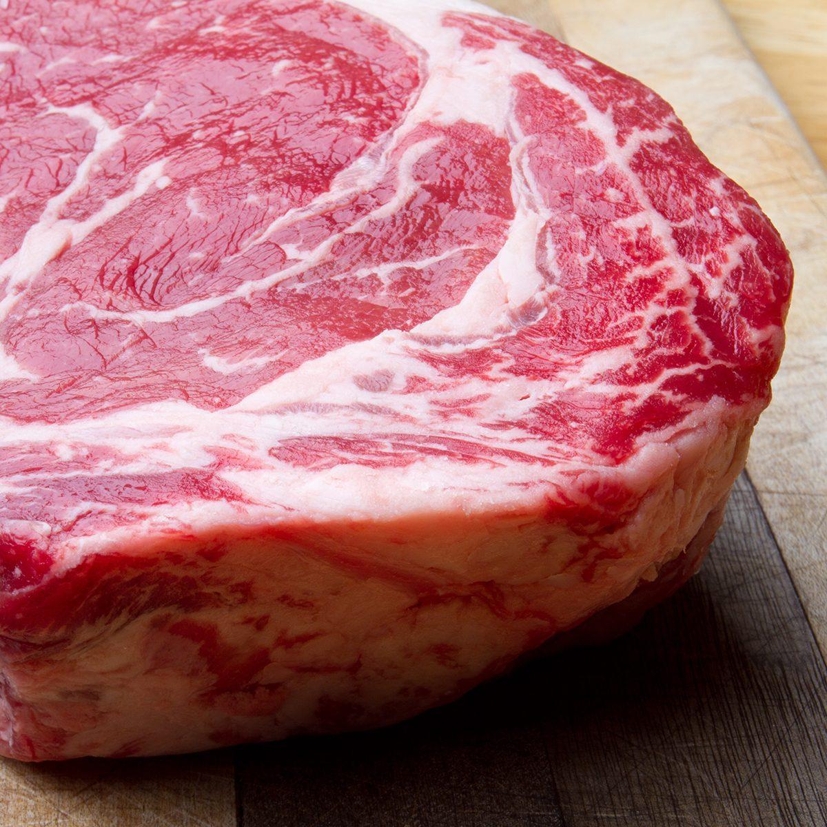 Thick Bone-In Rib Eye Steak on a cutting board